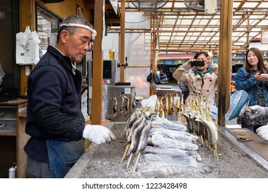 Oct 15th 2018: Nikko, Old man selling grilled fish in a stall to tourists, JAPAN