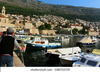 Oct. 20, 2018 - Dubrovnik, Croatia : Man paints landscape of boats and houses on the hill, and boats on the water in Dubrovnik, Croatia, on the Adriatic Sea, Europe
