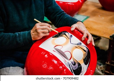 OCT 22, 2014 Takasaki, Gunma, Japan : A man making Daruma  - Traditional Japanese paper mache doll in Daruma workshop