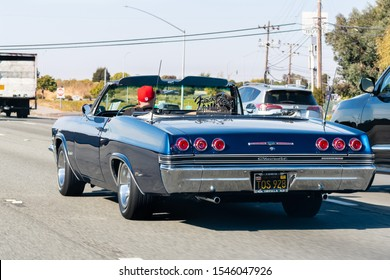 Oct 26, 2019 San Francisco / CA / US - 1965 Chevrolet Impala SS driving on the freeway; Frisco's Finest car club logo displayed on the car