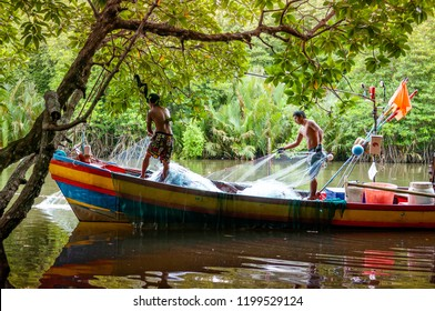 OCT 3, 2018 Trat, Thailand - Thai fisherman working with fishing net on wooden fishing boat in mangrove canal of Ban Nam Chiao - Trat province.