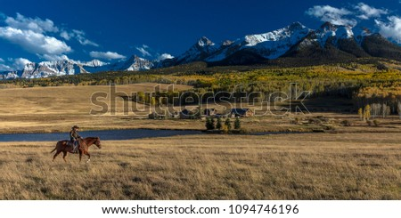 OCT 4, 2017, RIDGWAY COLORADO - Older Cowboy, Howard Linscott , leads packhorse across historic Last Dollar Ranch on Hastings Mesa, SW Colorado, San Juan Mountains