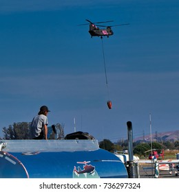 Oct.,15, 2017, Petaluma, CA. - A man sits on top of gas truck watching  firefighter helicopter land at Petaluma Municipal Airport being used by during the disastrous North Bay fires in Sonoma County.