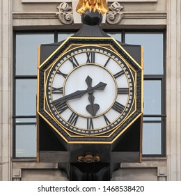 Octagonal clock at the facade of House of Fraser in King William Street in London, United Kingdom. Black fingers and numerals on white clock face. Time on clock: 05h42