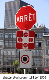 octagonal red and white stop street sign with French text (arrêt = stop) and square red and white sign indicating crossroad with 4 stop signs (each with french text arrêt = stop)