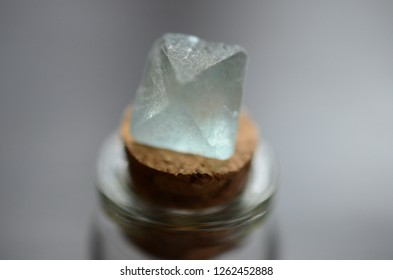 Octahedron Fluorite sitting on top of crystal vial. Macro photo of fluorite taken i natural lighting. Turquoise  and Lavender Fluorite Octahedrons.