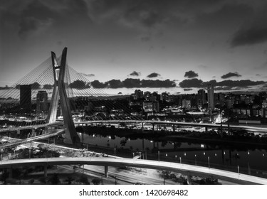 The Octavio Frias de Oliveira bridge is a cable-stayed bridge in Sao Paulo over the Pinheiros River in black and white