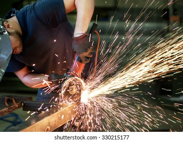 October 02, 2015 Monza, Lombardy, Italy : Metalworker cutting a steel bar using a handheld angle grinder power tool