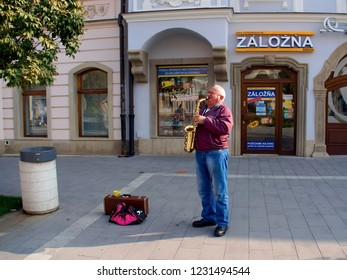 October 1, 2018, Trnava, Slovakia The older man stands in the street in front of a backup and plays the saxophone.Behind him is the entrance to the pawnshop.