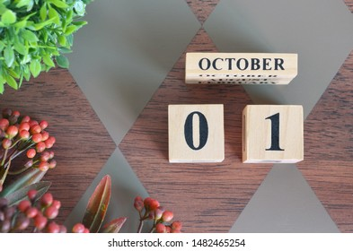 October 1. Date of October month. Number Cube with a flower and leaves on Diamond wood table for the background