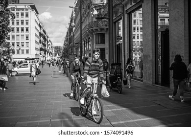 October 10, 2019 the city of Toulouse in France, two young guys ride a bicycle along the street of the old city.