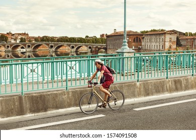 October 10, 2019 Toulouse city in France, a man rides a bicycle on a bridge against the background of the old city.