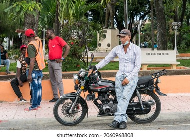 October 11, 2021 San Jose de Ocoa, Dominican Republic. Dramatic image of a Dominican man standing next to his motorbike in the Central Park of this mountain town, with Haitian's socializing.