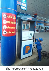 October 12, 2017 inside gasoline station and services in VIETNAM under the national brand picture shows a gas station worker at filling activity and a large warning poster with clear signs nearby