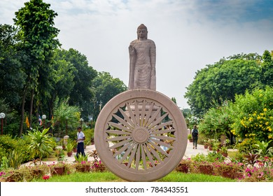 October 13, 2017. Sarnath, Varanasi, India. The Ashok Chakra with blurry background of Grand Statue of Buddha in WAT THAI Temple