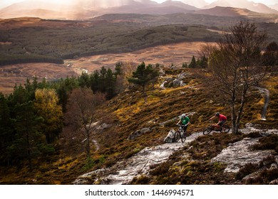 OCTOBER 15, 2007 - LAGAN, SCOTLAND. Two mountain bikers riding a rocky trail in dramatic highlands landscape with brown autumn colours