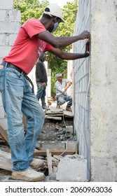 October 16, 2020 La Cienaga, Dominican Republic. Dramatic image of a Haitian and Dominican construction workers using a clear tube to level roof and set floors in a small Caribbean mountain town.