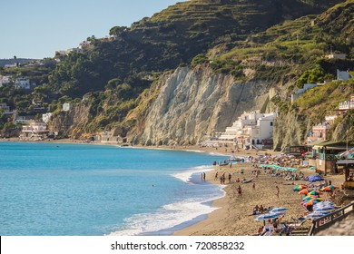 OCTOBER 16TH, 2016 - ISCHIA ISLAND, ITALY- Unknown tourists sunbathing on the beach of Ischia Island, Italy.  Colorful umbrellas line the beach.