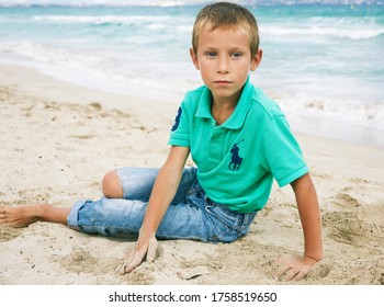 October 17, 2018 Portrait of a boy on the beach. The boy is wearing legendary Ralph Lauren polo shirt and blue jeans.