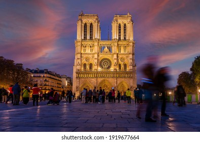 October 19, 2015: Parvis with tourists, and the facade of Notre Dame de Paris cathedral illuminated at night, in Ile de France, in France