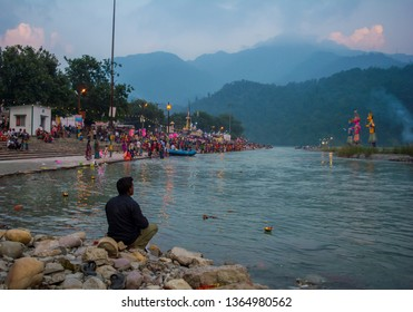 October 19, 2018/Rishikesh: one adult male sitting on the rocks alone by the river in an evening. Person is facing away from camera and is suffering from depression. There is ganga arti taking place