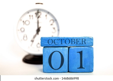 october 1st. Day 1 of month, handmade wood cube calendar and alarm clock on blue color. autumn month, day of the year concept.