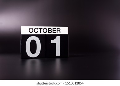 October 1st. Day 1 of month, wooden color calendar on black background. Autumn time. Empty space for text