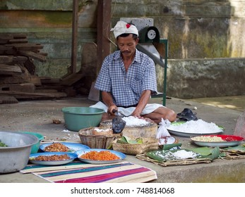 October 2014, Bangli, Bali, Indonesia: a man cuts vegetable and cooks food in preparation for a religious festival in ancient Hindu temple Pura Kehen.