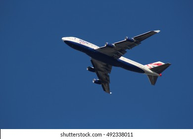 October 2016, London. A British Airways airplane carrying the branding for the oneworld airline alliance flies above London against a cloudless sky