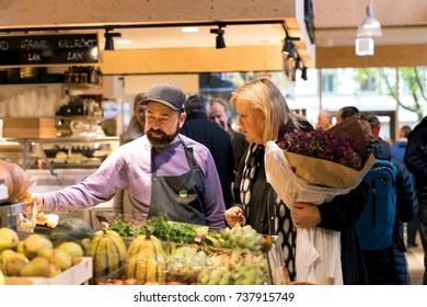 October 2017, Food market Ostermalmtorg in Stockholm, Sweden. Woman and the farm seller talk about vegetables