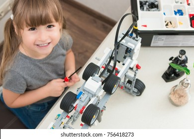 October, 2017. Minsk, Belarus. Little girl is behind the desk. Microscope, the tree, Lego robot mindstorms EV 3 are near her.  E-learning. Stem education. Cute child. Robotics. Elementary school.