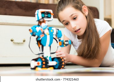 October, 2017. Minsk, Bularus. Schoolgirl is learning and playing with robot Lego Boost.  Chemical preparations in flasks and test tubes, a microscope. STEM education. Robotics. Robot.