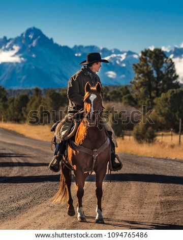 OCTOBER 2017, Ridgway, Colorado: Cowboy on Cattle Drive on long dirt road to San Juan Mountains and Mnt. Sneffels