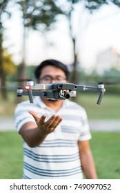 October 2017 - Shah Alam, Malaysia : A DJI Mavic Pro drone hovering in front of a guy in a park at sunset