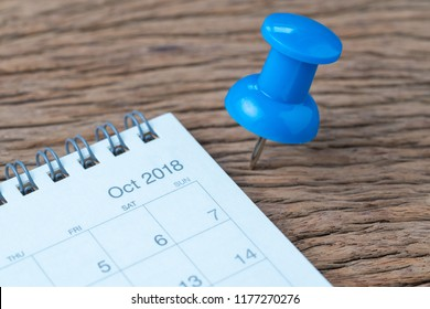 October 2018 calendar appointment, deadline, holiday or date planning concept, big blue pushpin or thumbtack pin on wooden table next to Sep white clean calendar.