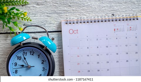 October 2018 calendar with retro clock on white wooden background. Autumn time and mood