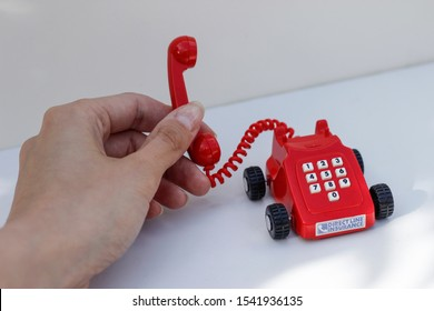 October 2019, Swansea, UK. Direct Line Car Insurance Company. Rotary Dial Style miniature red landline phone on wheels.