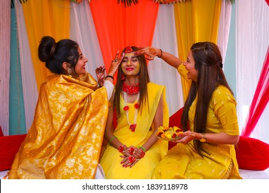 october 2020 new delhi, india Portrait of a beautiful Indian bride  with turmeric haldi paste on her face applied by her sisters.
