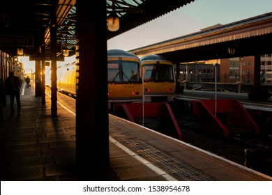 October 21. 2018 Moor Street Station, Bermingham, UK, Beautifual sunrise against the sun silhouette at railway station with old rustic vintage trains, people waiting for traveling to downtown city