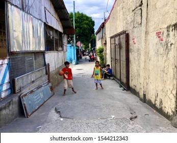 October 24, 2019 Manila, Philippines. The Filipino boy enjoy basketball game on a narrow street.