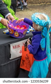 October 27, 2018 Coloma MI USA, a little girl dressed as a fairy takes candy during an outdoor Halloween event in Michigan USA
