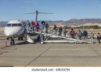 October 4, 2016 - Passengers climbing stairs to board airplane, Santa Barbara, CA