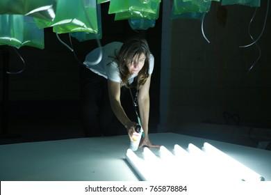 October 5, 2017, Toronto, Ontario, Canada.  Female scientist checks a display of algae bioreactors growing nutritional spirulina at EDIT event.  Expo of Design Innovation Technology.