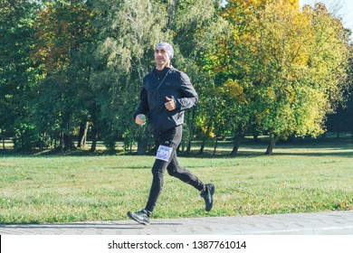 October 6, 2018 Novogrudok Belarus Castle Road Mature athlete with a number on his foot runs down the road