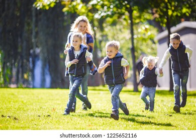October 6, 2018 Ukraine. Kiev. theme family outdoor activities. big friendly Caucasian family six mom dad four children playing football, running ball on lawn, green grass lawn near house sunny day.