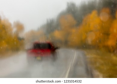OCTOBER 8, 2018 USA - Colorado/New Mexico Highway 17 in rain - Red pickup truck drives in rain road dotted with autumn colored yellow trees
