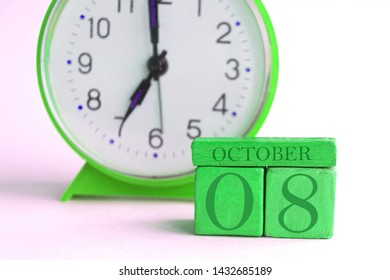 october 8th. Day 8 of month, handmade wood cube calendar and alarm clock on light green color. autumn month, day of the year concept.