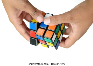 October 9, 2019. Mumbai, India. Closeup of (Indian - Asian) youth's hands playing with Rubik's/Rubic's  cube isolated against plain white background.