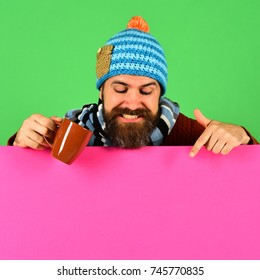 October beverage idea. Hipster with beard and smiling face has warm tea or coffee pointing down. Autumn and cold weather concept. Man in hat holds brown cup on green and pink background, copy space
