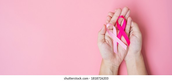 October Breast Cancer Awareness month, adult Woman  hand holding Pink Ribbon on pink background for supporting people living and illness. International Women, Mother and World cancer day concept
